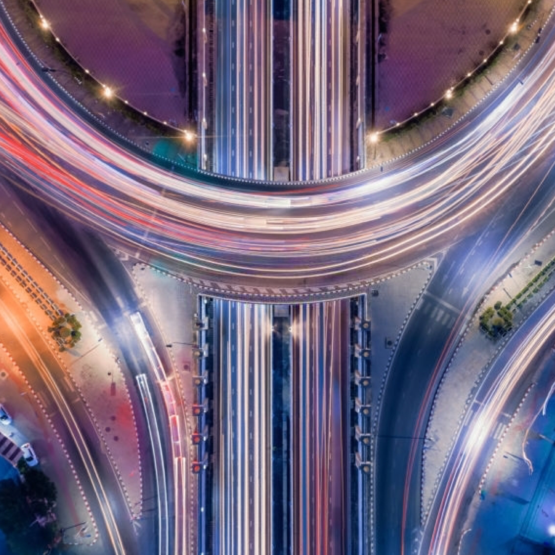 Overhead image of a colorful freeway overpass with streaks of multicolored light on the roads