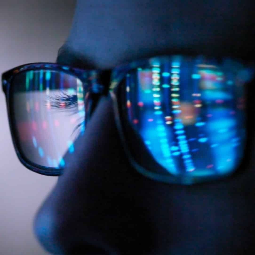 Closeup image of a man's glasses reflecting multicolored data visualization on a computer screen